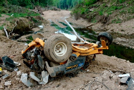 A cub cadet destroyed by the flood and pulled from the creek bed by a private contractor hired by the city now sits overturned and abandoned on private property.